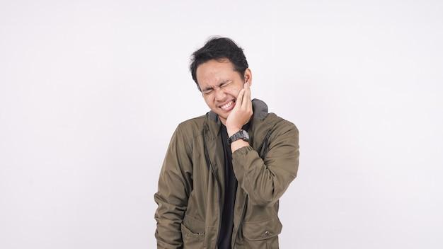 Mal di denti dell'uomo asiatico su uno spazio bianco