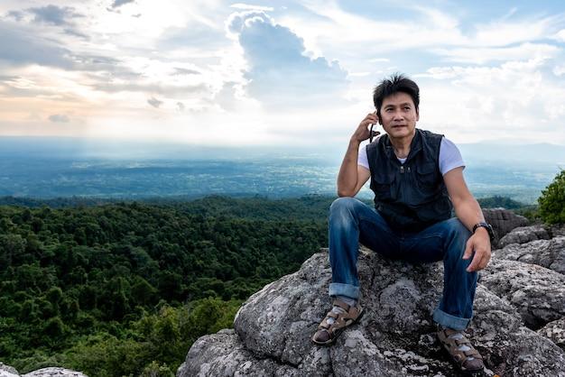 Turisti uomo asiatico utilizzando il telefono cellulare parla con gli amici mentre era in cima alla montagna