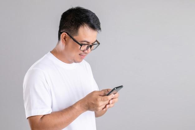 Uomo asiatico che digita o che chiacchiera sullo smartphone