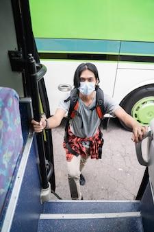 Uomo asiatico verso l'alto che indossa la maschera per il viso e zaino in procinto di prendere l'autobus alla stazione degli autobus. concetto covid-19