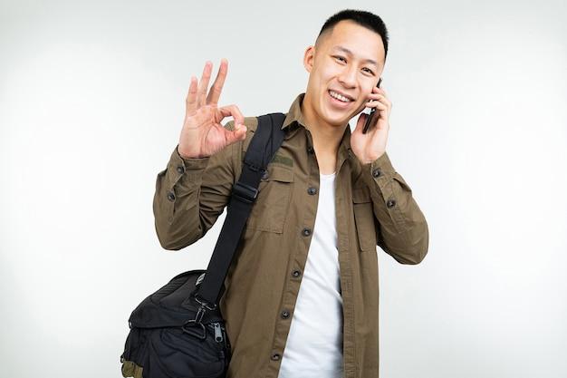 L'uomo asiatico in abiti urbani con una borsa discute di affari al telefono