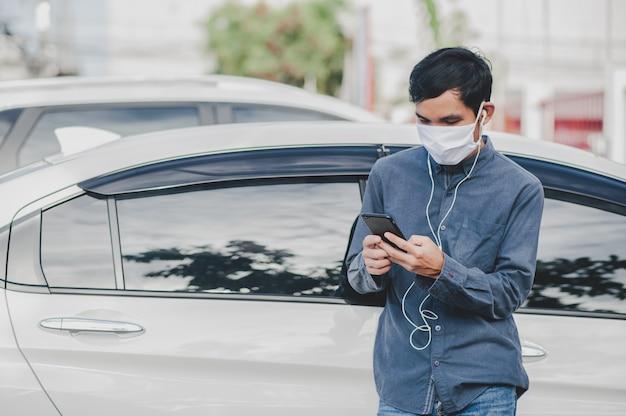 La maschera di protezione asiatica di uso dell'uomo è videochiamata sul telefono cellulare che sta all'automobile nel fuoco della città sul telefono