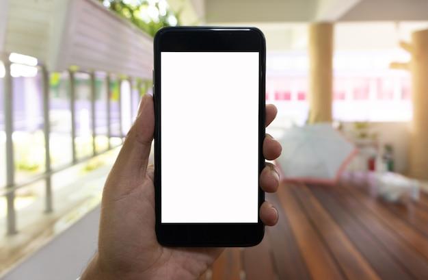 Uomo asiatico utilizzando smartphone nero della stretta della mano, priorità bassa di mockup di smartphone.