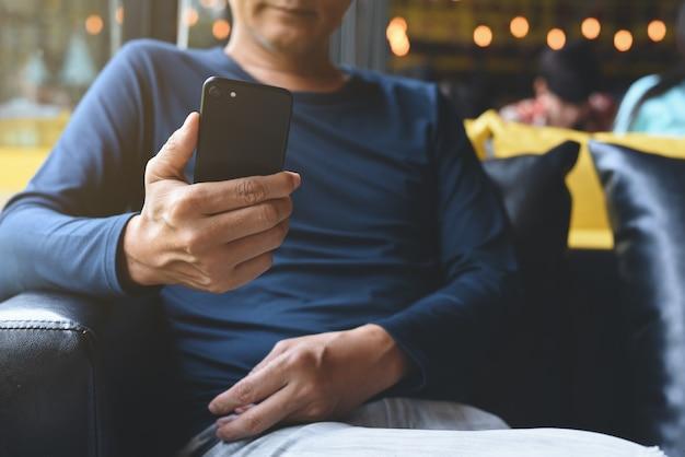 Uomo asiatico che utilizza smartphone nel caffè