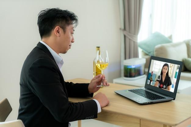 Uomo asiatico virtual happy hour meeting party e bere vino d'uva bianca online insieme