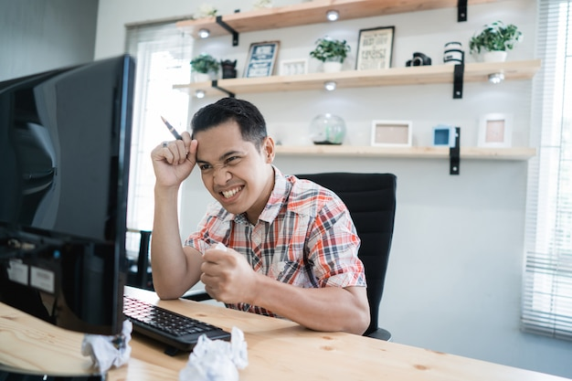 Uomo asiatico che aspetta qualcosa che esamina pc