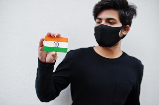 L'uomo asiatico indossa tutto nero con la maschera per il viso e tiene in mano la bandiera dell'india isolata su bianco. coronavirus concetto di paese.