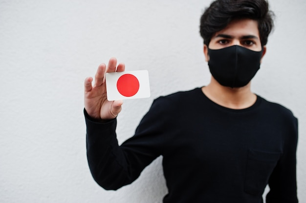 L'uomo asiatico indossa tutto nero con la maschera per il viso e tiene in mano la bandiera del giappone isolata su bianco. coronavirus concetto di paese.