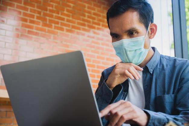 L'uomo asiatico indossa una maschera per il viso con un computer funzionante a casa, trading online a casa