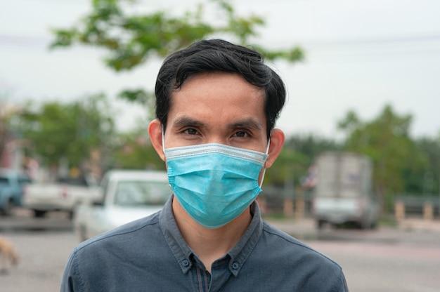 L'uomo asiatico indossa una mascherina medica nello stile di vita nuovo normale per proteggere il virus corona covid 19