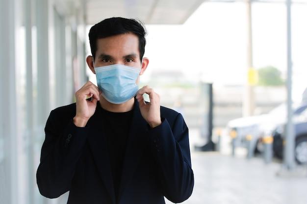 L'uomo asiatico indossa una maschera medica per proteggere il coronavirus covid 19 che cammina per strada, lo stile di vita urbano è una nuova normalità