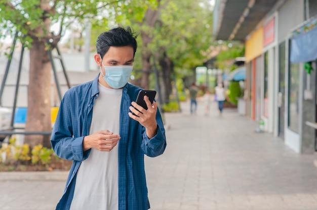 Uomo asiatico indossare maschera medica utilizzando smartphone camminando sulla strada