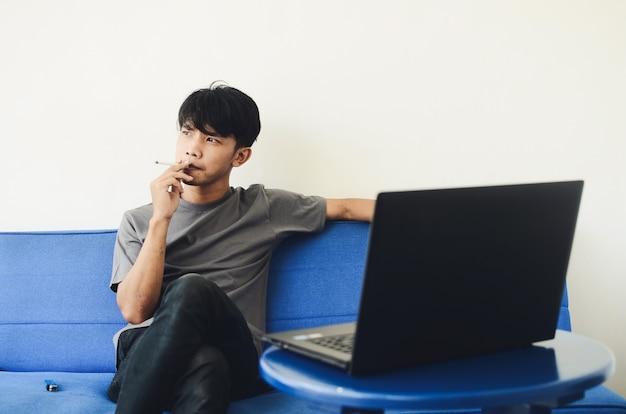 L'uomo asiatico che indossa una camicia di cenere fuma sul divano