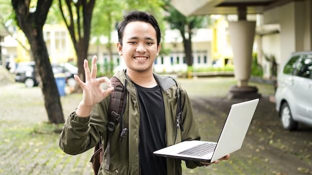Uomo asiatico che indossa una borsa mentre si tiene un computer portatile con il gesto giusto