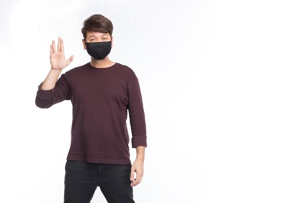 L'uomo asiatico che indossa una maschera nera fa vulcan salute, un nuovo saluto normale