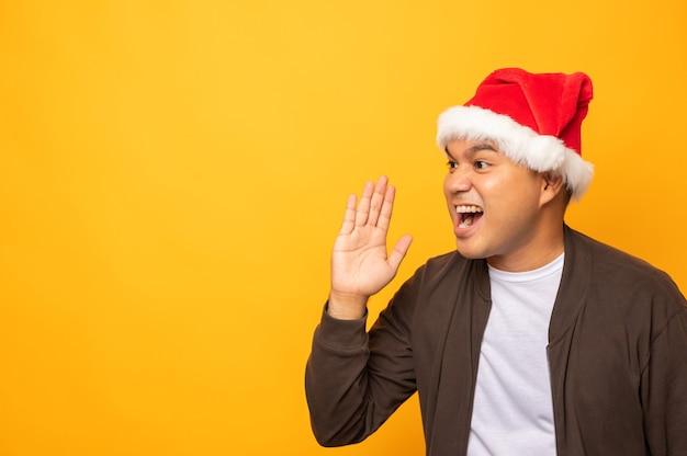 Uomo asiatico che indossa cappello di natale e grida