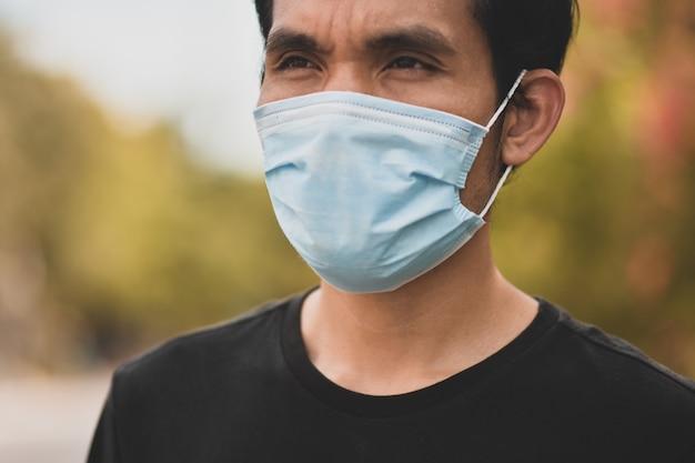 Uomo asiatico un concetto di maschera facciale da portare nuovo normale allontanamento sociale