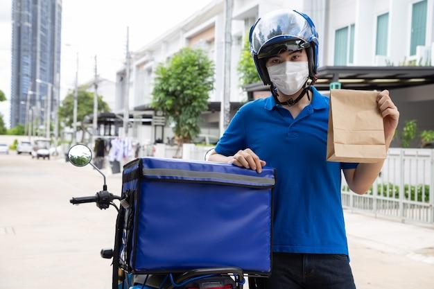 Uomo asiatico che indossa una maschera facciale e tiene in mano un sacchetto di carta per alimenti e sta in piedi sul lato della scatola di consegna