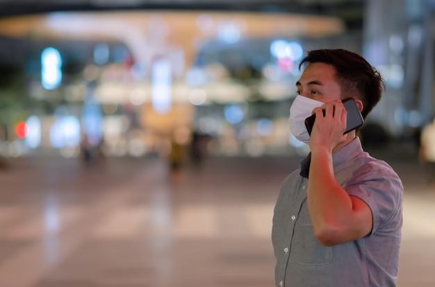 Uomo asiatico che indossa la maschera per il viso ed effettua una chiamata con lo smartphone.
