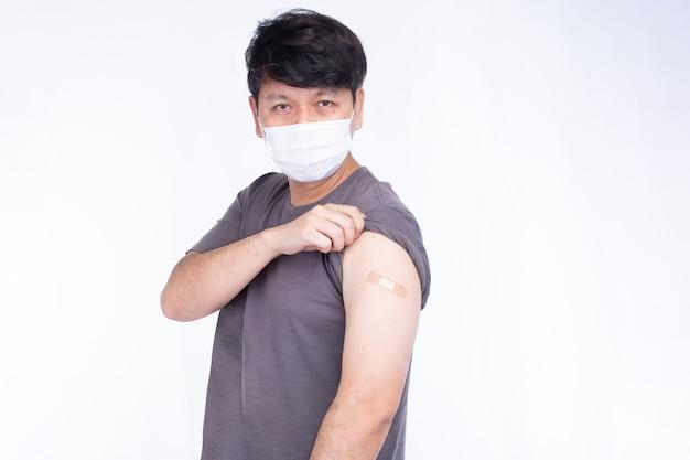 L'uomo asiatico che indossa la maschera facciale apre la manica per mostrare la spalla con la benda dopo aver ottenuto l'immunizzazione covid-19 della vaccinazione, mostra i colpi isolati su sfondo bianco
