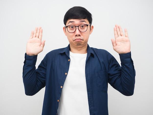 L'uomo asiatico con gli occhiali mostra la mano per il gesto di resa ritratto sfondo bianco
