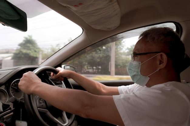 Uomo asiatico che indossa una maschera medica durante la guida