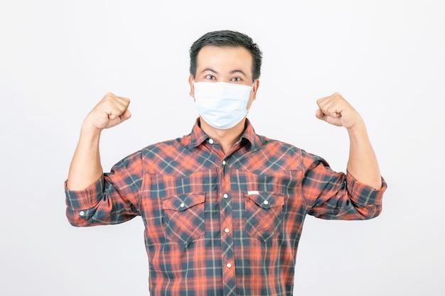 Uomo asiatico che indossa la maschera protettiva in azione di vittoria