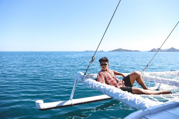 Uomo asiatico che indossa occhiali da sole che si rilassano sulla rete del catamarano godendosi l'ora legale
