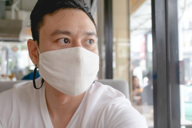 L'uomo asiatico indossa una maschera bianca per la protezione da virus covid in un caffè pubblico.