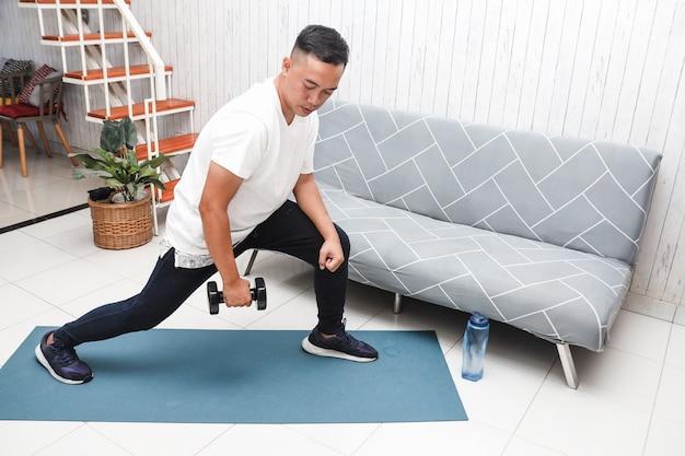 Uomo asiatico in camicia bianca su tappetino blu che solleva pesi con mini manubri a casa