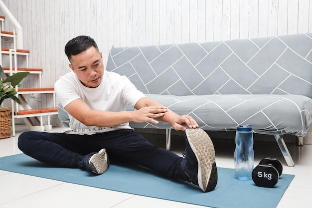 L'uomo asiatico in camicia bianca sul tappetino blu fa esercizi di stretching a casa