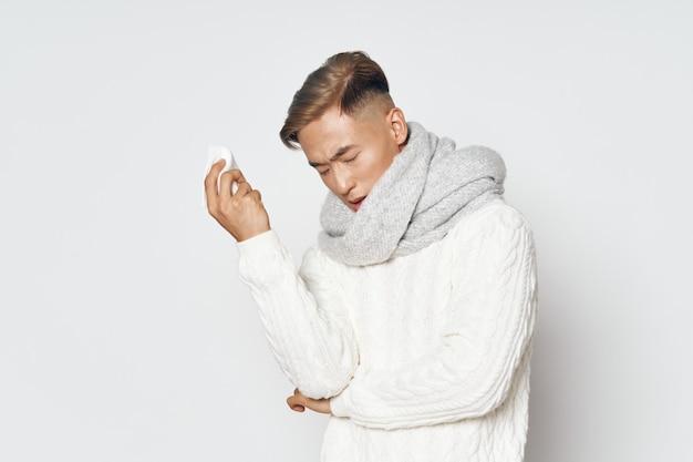 Uomo asiatico con un maglione bianco con una sciarpa intorno al collo su uno sfondo chiaro