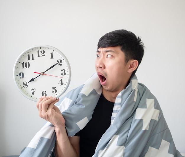 L'uomo asiatico con il corpo coperto da una coperta si sveglia tardi si sente scioccato e guarda l'orologio in mano