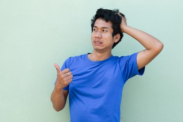 Uomo asiatico con la faccia noiosa esagerata e guardando il lato