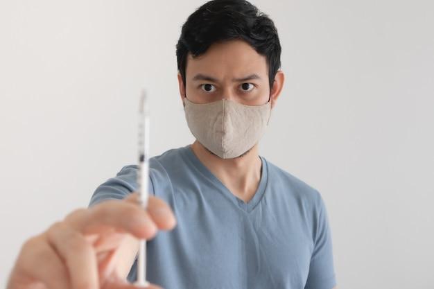 L'uomo asiatico con una maschera facciale sta iniettando un vaccino. concetto di protezione antivirus.