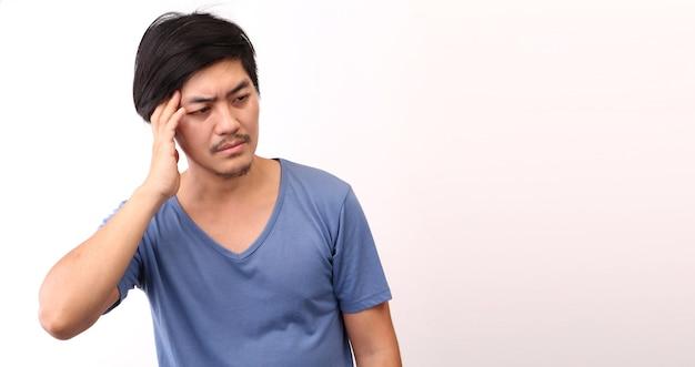 Uomo asiatico con un mal di testa su sfondo bianco in studio.