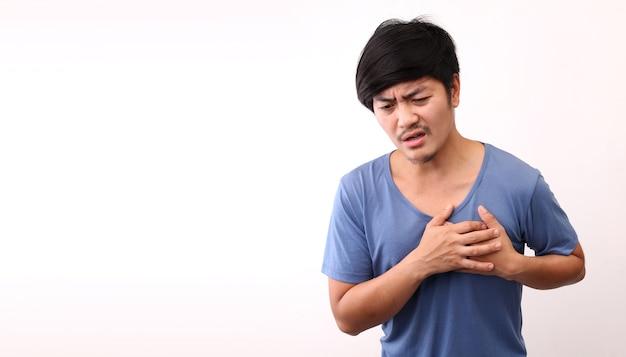 Uomo asiatico con dolore al cuore su sfondo bianco in studio con copia spazio.