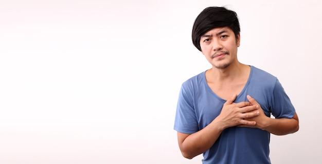 Uomo asiatico con dolore al cuore su sfondo bianco.