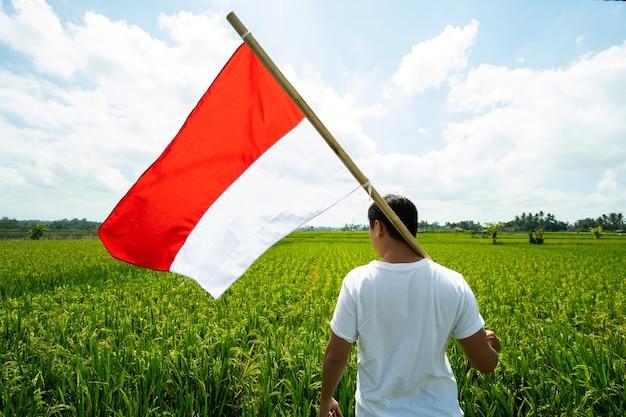 Uomo asiatico con la bandiera indonesiana dell'indonesia in cima alla montagna