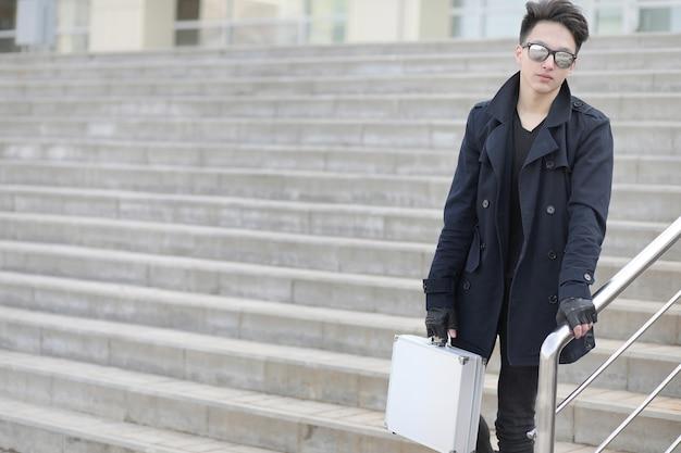 Uomo asiatico con una valigia di metallo in città custodia asiatica e argento asiatico con una valigia per tangenti