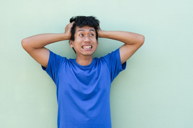 Uomo asiatico con preoccupazione shock overacting viso e alzare le mani sulla testa guardando in alto