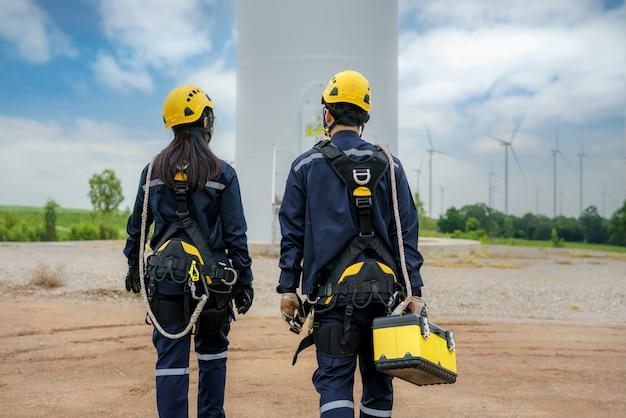 Uomo asiatico e donna ispezione ingegneri che preparano e controllo dei progressi di una turbina eolica con sicurezza in un parco eolico in thailandia.