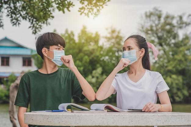 L'uomo e le donne asiatiche tornano a scuola con una maschera per il viso e si stringono la mano per mantenere le distanze sociali normali e senza contatto