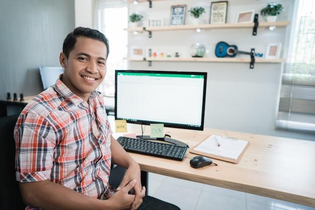 Lavoratore asiatico dell'uomo rilassato davanti allo scrittorio del computer