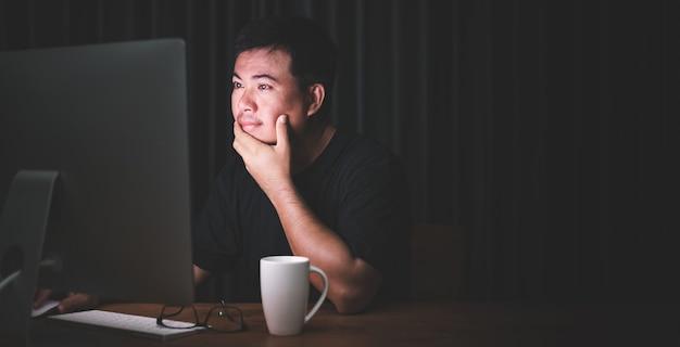 Uomo asiatico che lavora al computer