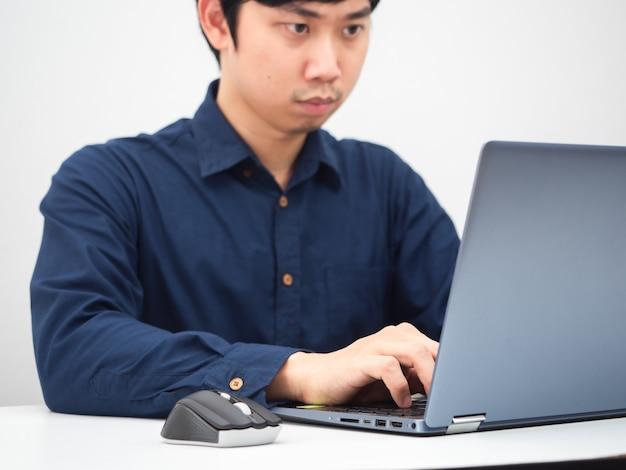 Uomo asiatico che lavora con il suo computer portatile sul tavolo a casa