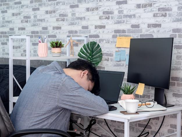 Uomo asiatico che lavora con il computer portatile nella sua stanza, condominio.