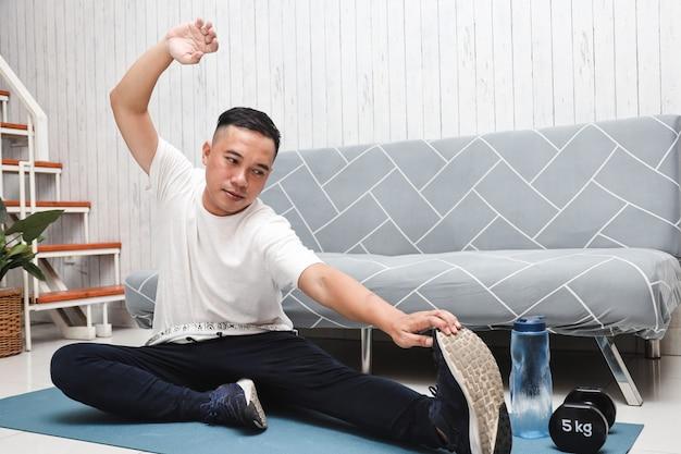 L'uomo asiatico sul tappetino da yoga fa esercizi di stretching a casa
