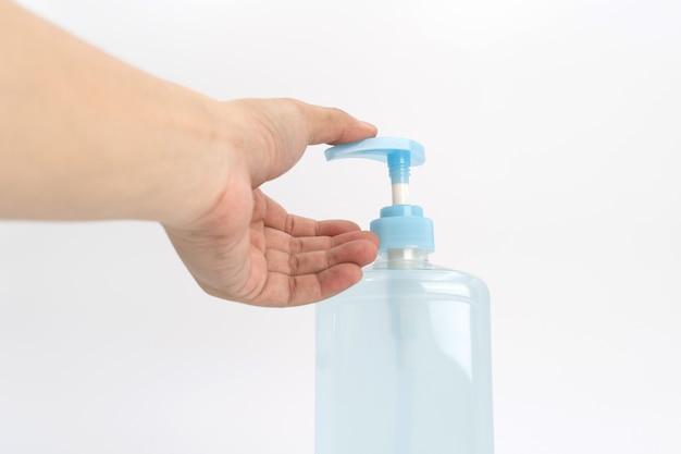 La mano asiatica del mand tiene una bottiglia della pompa dell'alcool gel e pronta a spingere su di essa