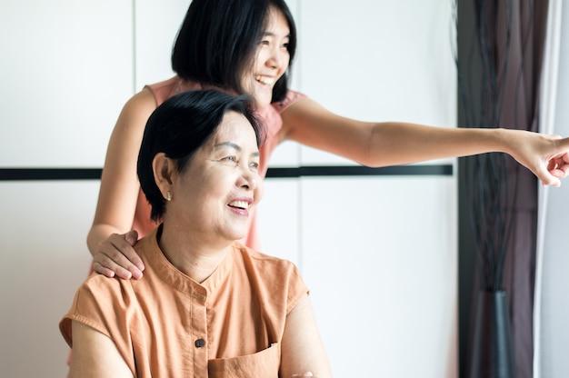 Donna matura asiatica felice con la figlia che si prende cura e supporto a casa, mamma anziana felice di mezza età, concetto di assicurazione senior